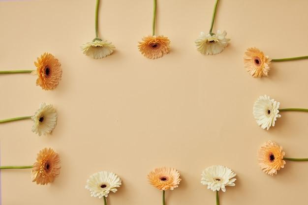 Een frame gemaakt van beige en oranje gerbera's op een beige achtergrond als lay-out voor een postkaart op valentijnsdag of moederdag met kopieerruimte. bovenaanzicht