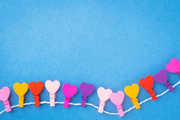 Een frame van gekleurde houten harten die op een kabel op een blauwe achtergrond hangen.