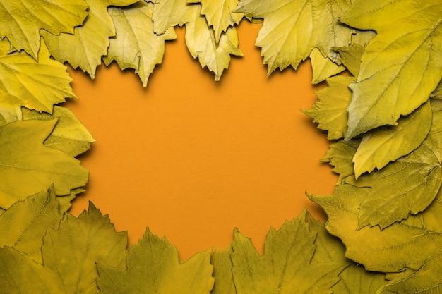 Een frame van gele herfstbladeren op een oranje achtergrond. ruimte voor de tekst. plat leggen.