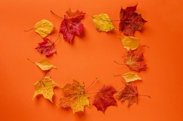 Een frame van herfstbladeren op een oranje achtergrond herfstbanner met kopieerruimte