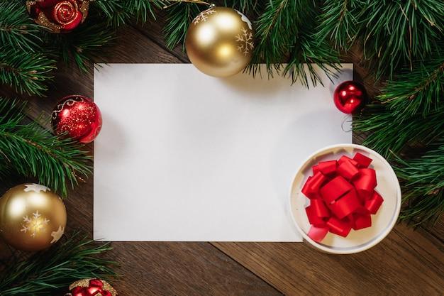 Een frame van pijnboomtakken en kerstversiering en a4-vel wit papier op een houten tafel. vakantie kerstmis. copyspace. uitzicht van boven.