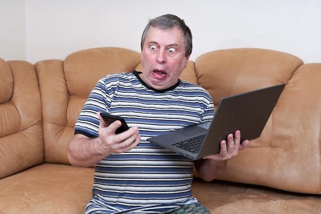 Een freak met een verbaasd gezicht houdt een laptop in zijn handen terwijl hij op de bank zit Premium Foto