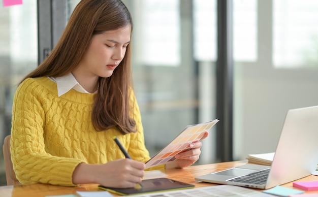 Een freelance ontwerper houdt een kleurenlader in de hand en schetst op een digitale tablet.