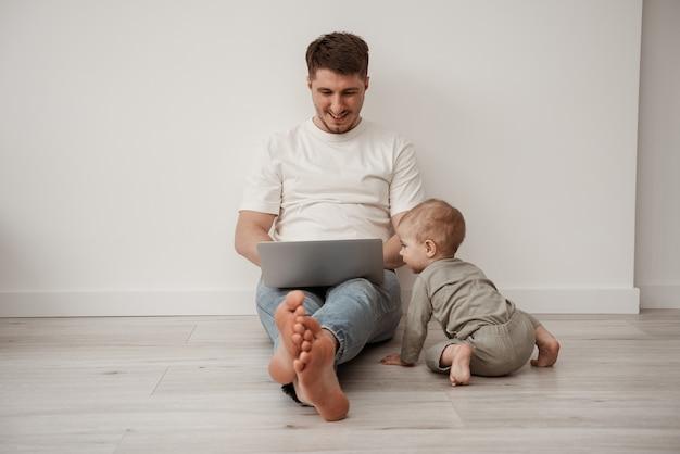 Een freelance vader zit op de grond bij een witte muur en doet zijn werk op een laptop, hij zit in afzondering dankzij ñovid-19, probeert thuis te werken maar wordt afgeleid door een klein kind
