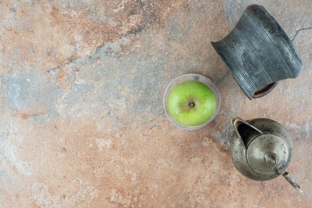 Een frisse appel met een oude kopjes op marmeren tafel.