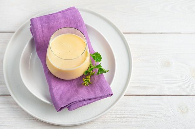 Een frisse, koele drank gemaakt van melk, yoghurt, water en mango op een lichte muur. lassi, yoghurt, cocktail-verfrissende gezonde drankjes.