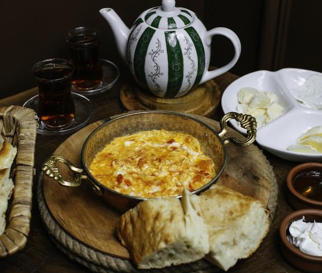 Een front close-up ontbijttafel met gekookte eieren en met hete thee op de bruine vloer