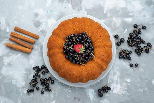 Een fruitcake van bovenaanzicht, heerlijk en rond gevormd met vers blauw, bessen op heldere zoete suiker van het cakekoekje