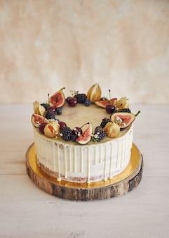 Een fruitige verjaardagstaart met verjaardagstopper, fruit bovenop en witte druppel op een beige muur