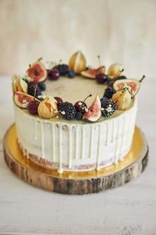 Een fruitige verjaardagstaart met verjaardagstopper, fruit erop en witte druppel op een beige achtergrond