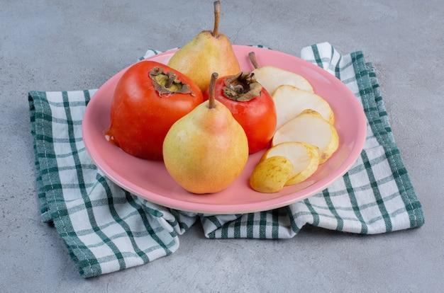 Een fruitschaal met peren en dadelpruimen op een handdoek, op marmeren achtergrond.