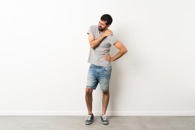 Een full-length shot van een knappe man met baard die pijn in de schouder heeft omdat hij zich heeft ingespannen