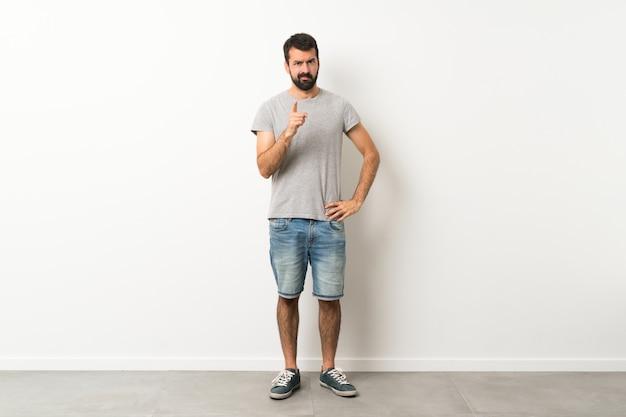 Een full-length shot van een knappe man met baard gefrustreerd en naar voren wijzend