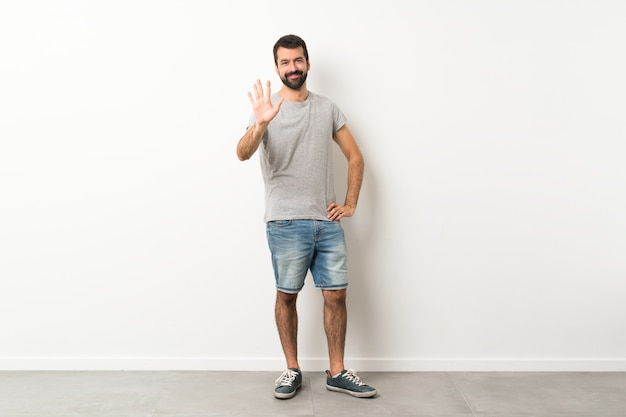 Een full-length shot van knappe man met baard tellen vijf met vingers