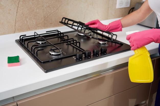 Een gasfornuis schoonmaken met keukengerei, huishoudelijke concepten of hygiëne en schoonmaak.