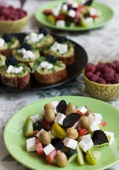 Een gastronomische lunch voor twee: sandwiches met guacamole, frambozen en een griekse salade.