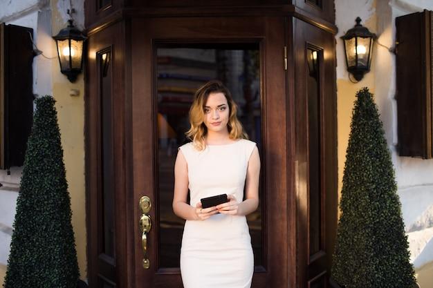 Een gastvrouw staat met een tablet en begroet gasten.