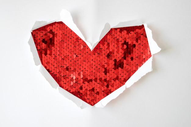 Een gat van rode pailletten met gescheurde zijkanten in de vorm van een hart op een witte achtergrond voor kopie ruimte. wenskaart voor valentijnsdag, vrouwendag of bruiloft uitnodiging.