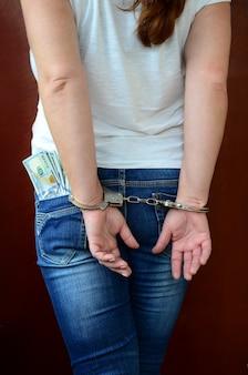Een gearresteerd meisje met geboeide handen met een enorme hoeveelheid dollarbiljetten