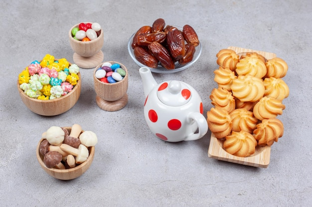 Een geassorteerde set koekjes, dadels, snoepjes en chocoladepaddestoelen naast een kleine theepot op marmeren oppervlak.