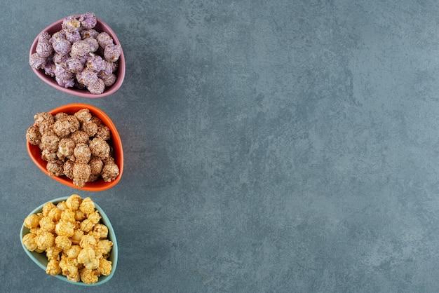 Een geassorteerde verscheidenheid aan popcorn snoep kleuren geassorteerd in kleine kommen op marmeren achtergrond. hoge kwaliteit foto