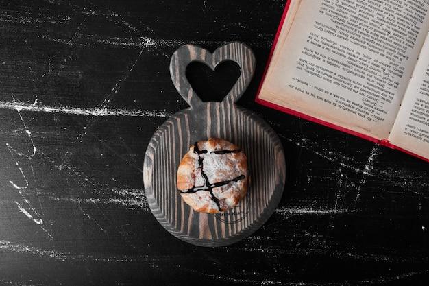 Een gebakje broodje met chocoladesiroop op een houten bord.