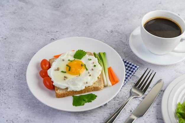 Een gebakken ei tot op een toast, gegarneerd met peper zaden met wortelen en lente-uitjes.