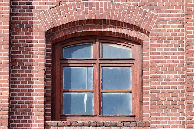 Een gebogen glazen raam op oude rode bakstenen muur