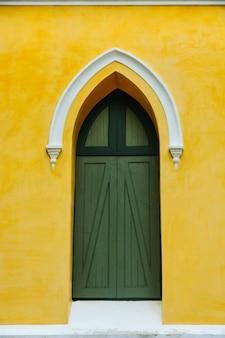 Een gebogen groene houten deur versier wit stucwerk in de gele fresco gips cement muurafwerking