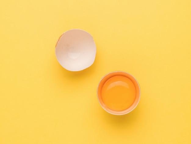 Een gebroken ei op een gele achtergrond. een natuurproduct.