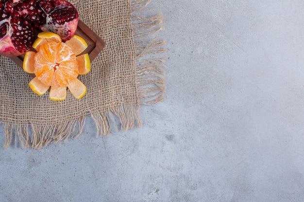 Een gebroken granaatappel en een gepelde mandarijn op een stuk doek op marmeren achtergrond.