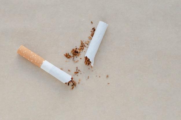 Een gebroken sigaret op een papieren achtergrond. verspreide tabak.