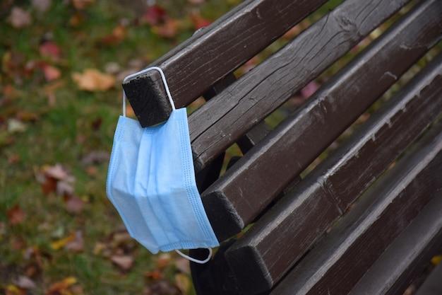Een gebruikt beschermend medisch masker hangt aan een houten parkbank. het probleem van milieuverontreiniging als gevolg van een pandemie