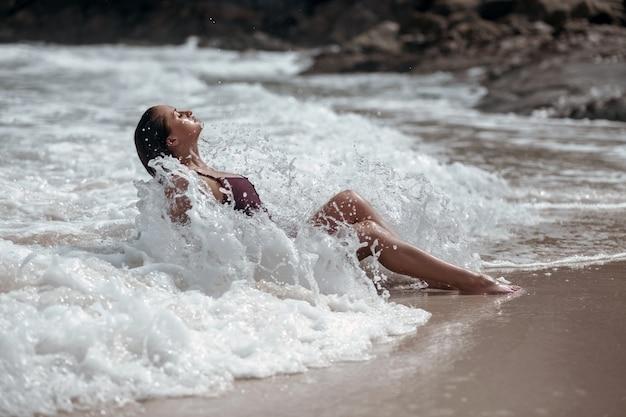 Een gebruinde, jonge schoonheid baadt in de golven van de zee en sluit haar ogen.