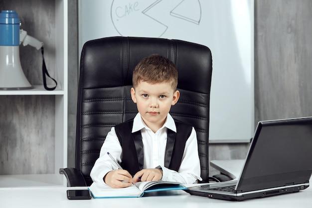 Een geconcentreerd kind dat aan het bureau van de bureaudirecteur werkt.