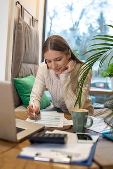 Een geconcentreerde vrouw die belastingen en uitgaven berekent voor haar bedrijf