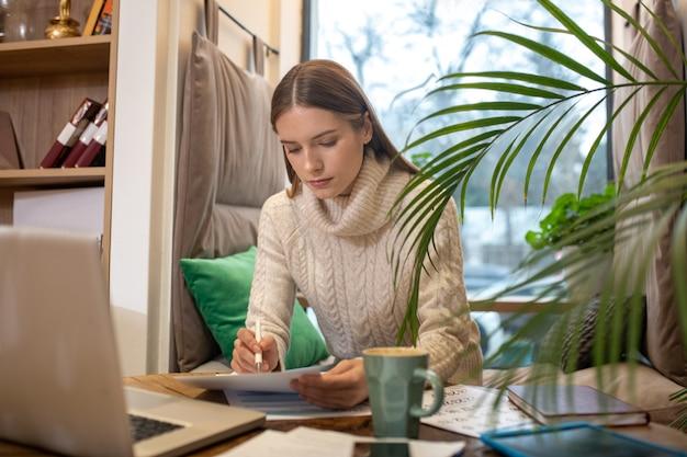 Een geconcentreerde vrouw die werkt met een belangrijk papier