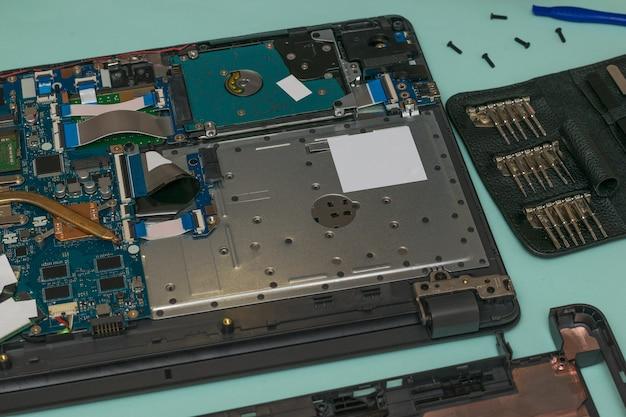 Een gedemonteerde laptop en een set reparatiehulpmiddelen op een blauwe tafel.
