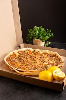 Een gedistribueerd vooraanzicht lahmacun deeg met gehakt samen met greens en citroen in papier doos smakelijke gebak maaltijd
