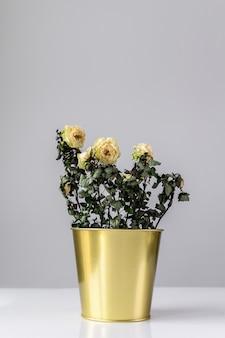 Een gedroogde roos in een gouden pot