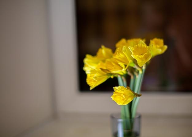 Een geel boeket narcissen in een glazen vaas op de vensterbank in de kamer. een leuk cadeau voor je geliefde