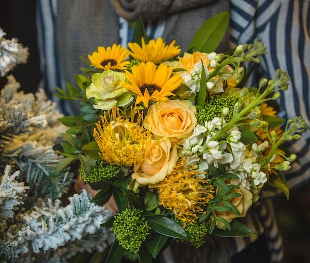 Een geel boeket zonnebloemen en rozen in handen van een dame