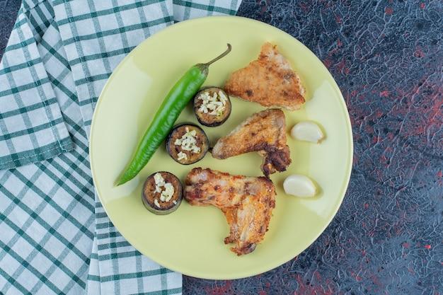 Een geel bord kipnuggets met groenten.
