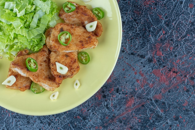 Een geel bord kippenvlees met slasalade.