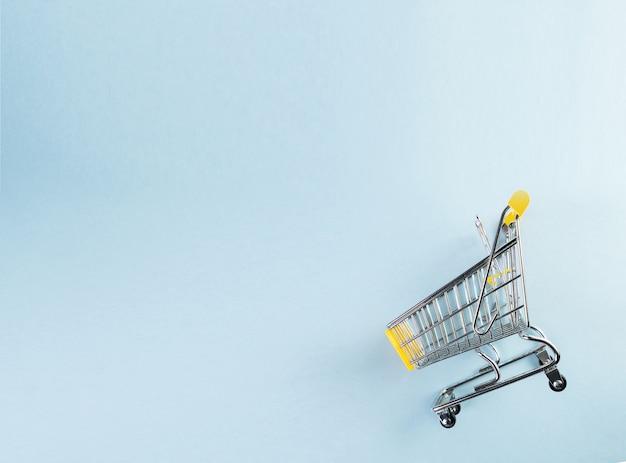 Een geel leeg miniboodschappenwagentje op pastelkleur blauwe achtergrond. winkelen concept.