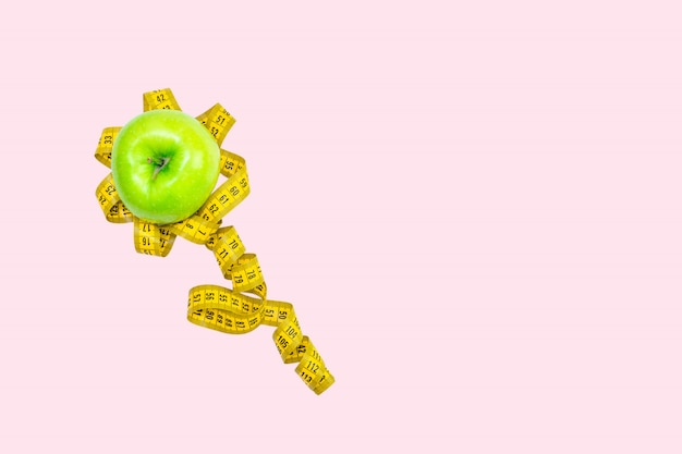 Een geel meetlint en een groene verse appel liggen in de vorm van een bloem. creatief concept van dieet, vermagering, gewichtsverlies, zwaarlijvigheid, lichaamscontrole op een roze achtergrond.