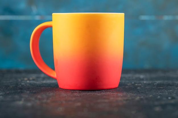 Een geel met rood gekleurde mok om te drinken