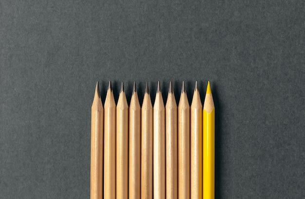 Een geel potlood dat opvalt uit de reeks grijze potloden