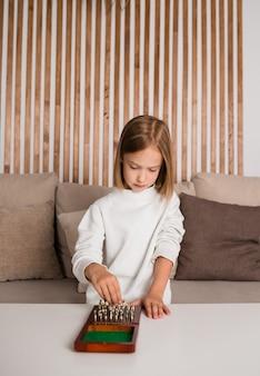 Een gefocust blond meisje zit op de bank en speelt schaak aan een tafel in de kamer