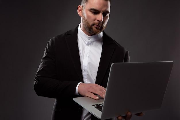 Een gefocuste zakenman werkt met een laptop die hij in zijn hand houdt.
